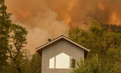 house on hillside with wildfire smoke in background